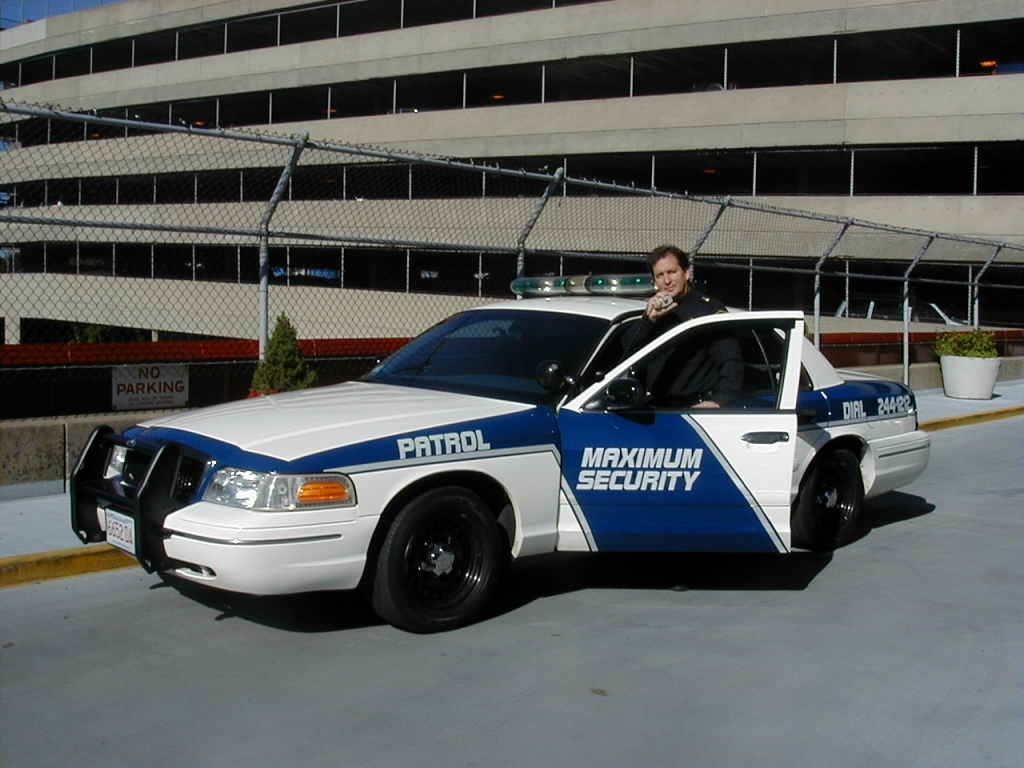 Maximum Security, Inc. guard in full uniform in patrol car