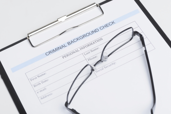 Close-up of criminal background check document with a eyeglasses lying on it